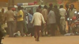 People stand near police car in Niger