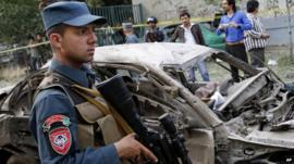 An Afghan Police man stands guard at the scene of a suicide car bomber attack that struck outside the Afghan Supreme Court in Kabul