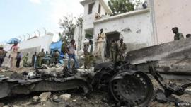 Security agents stand near the scene of a suicide bomb attack outside the United Nations compound in Somalia