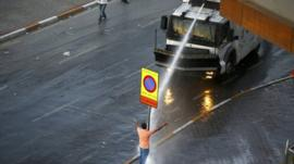 Water cannon is fired at a protester