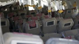 Inside Asiana Flight 214 oxygen masks can be seen hanging from the ceiling
