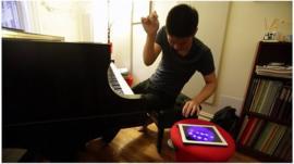 Conrad Tao playing the piano and ipad