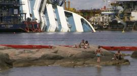 People in sea with Costa Concordia in the background