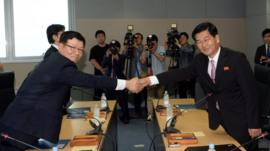 South Korea's working-level chief delegate Suh Ho (L) shakes hands with his North Korean counterpart Park Chul-su (R) during talks at the Kaesong industrial complex in North Korea