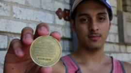 Man holds a GPS tracking coin
