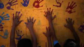 Young Syrian refugees touch colourful handprints on a mural that they made on one of the public bathrooms at Zaatari refugee camp