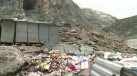 Waste strewn outside a path to the cave
