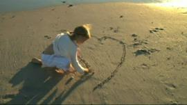 Girl drawing heart in sand