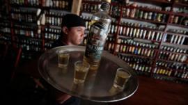 A waiter serves a bottle of cachaca, Brazil's national spirit