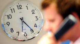 An office worker speaks on a telephone in front of a clock