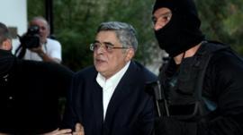 Nikolaos Michaloliakos being taken into court