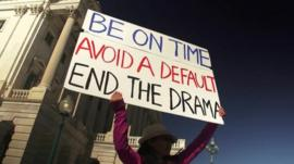 Woman holding up placard against the government shutdown