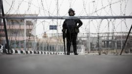 A riot policeman stands guard outside the complex where the trial will take place