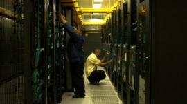 Two men work with computer servers