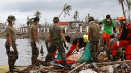 Military personnel and members of the Philippines Special Reaction Unit search for the bodies of victims near Tacloban