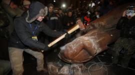 Protesters attacking toppled statue of Lenin