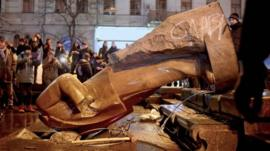 People surround a statue of Soviet state founder Vladimir Lenin, which was toppled by protesters during a rally organized by supporters of EU integration in Kiev