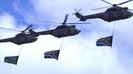 Military helicopters fly over the site at Qunu