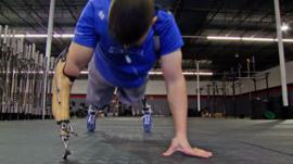 Injured US Army soldier Larkin O'Hern does push ups with prosthetic arm.