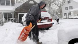 Man and woman digging out driveway