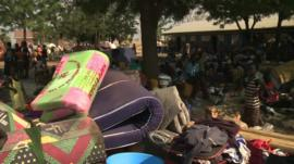 Mattresses and people in a refugee camp
