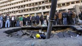 An Egyptian fire fighter checks a crater made by a blast at the police headquarters in Cairo