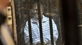 In this Tuesday, Jan. 28, 2014 photo, Egypt's ousted President Mohammed Morsi stands inside a glassed-in defendant's cage