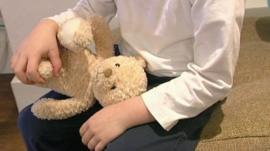 Child holding a teddy