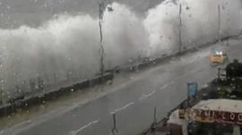 Police car being smothered by waves on Penzance promenade