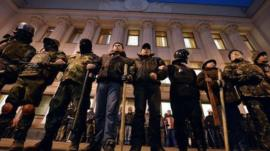 Maidan self-defence activists stand guard in front of the Ukrainian parliament during a session, in Kiev, on 24 February 2014.