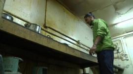 Migrant worker in unclean kitchen