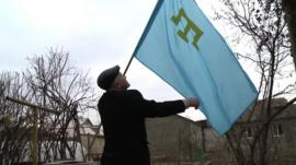 Rasim Bekirov with the flag of the Crimean Tatar people