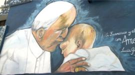 A mural featuring Pope Francis kissing a baby