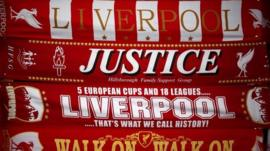 Liverpool scarves, including one asking for justice for the victims of the Hillsborough disaster, for sale on a stall in Liverpool on 26 March 2014