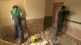 Builders stripping plaster from walls