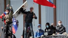 Pro-Russian activists who seized the main administration building in the eastern Ukrainian city of Donetsk hold Russian flag and flag of so-called