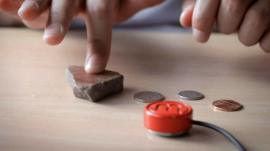 A person using a Mogees to turn a stone into a musical instrument