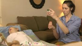 Nicole Mattison administers a drug to her baby daughter