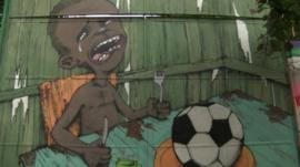 Street art in Brazil showing a boy with a football on his plate