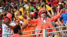 Netherlands fan dressed in orange with fake World Cup trophy