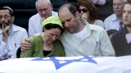 Avi and Rachel Frenkel embrace during the funeral of their son, Naftali Frenkel