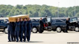 Dutch military personnel carry a coffin containing remains