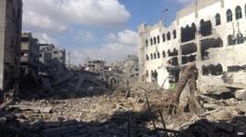 Resident in Shejaiya sift through rubble