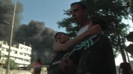 A man carries another man after Israeli strike