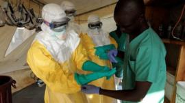 People wearing protective clothing in a West African country affected by the outbreak