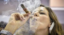 Woman smokes Cuban cigar at cigar festival in Havana on 27 February 2014