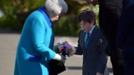 Queen being handed flowers by schoolboy