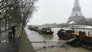 A man under an umbrella looks at the flooded river Seine level in front of the Eiffel tower in Paris on 23 January 2018