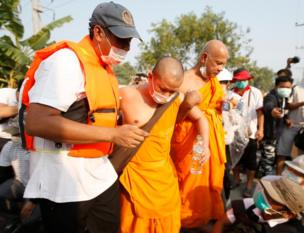 An injured Thai Buddhist monk of Dhammakaya Temple is helped after clashes with police officers outside the temple in Pathum Thani province, on the outskirts of Bangkok, Thailand, 20 February 2017