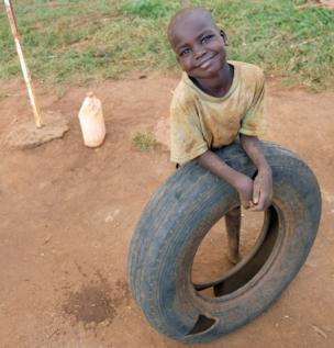 Un niño con una llanta sonríe